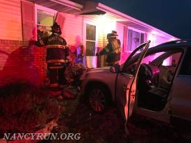 Rescue company investigating a structure after a vehicle collision into a house.
